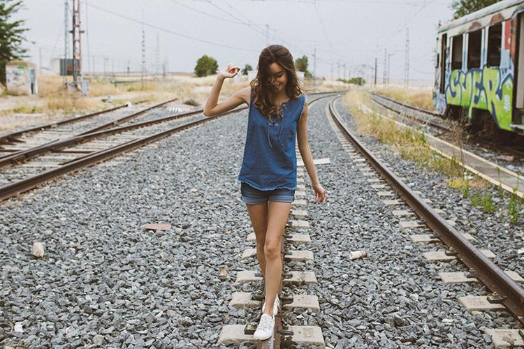 Beautiful young girl walking on the railway.